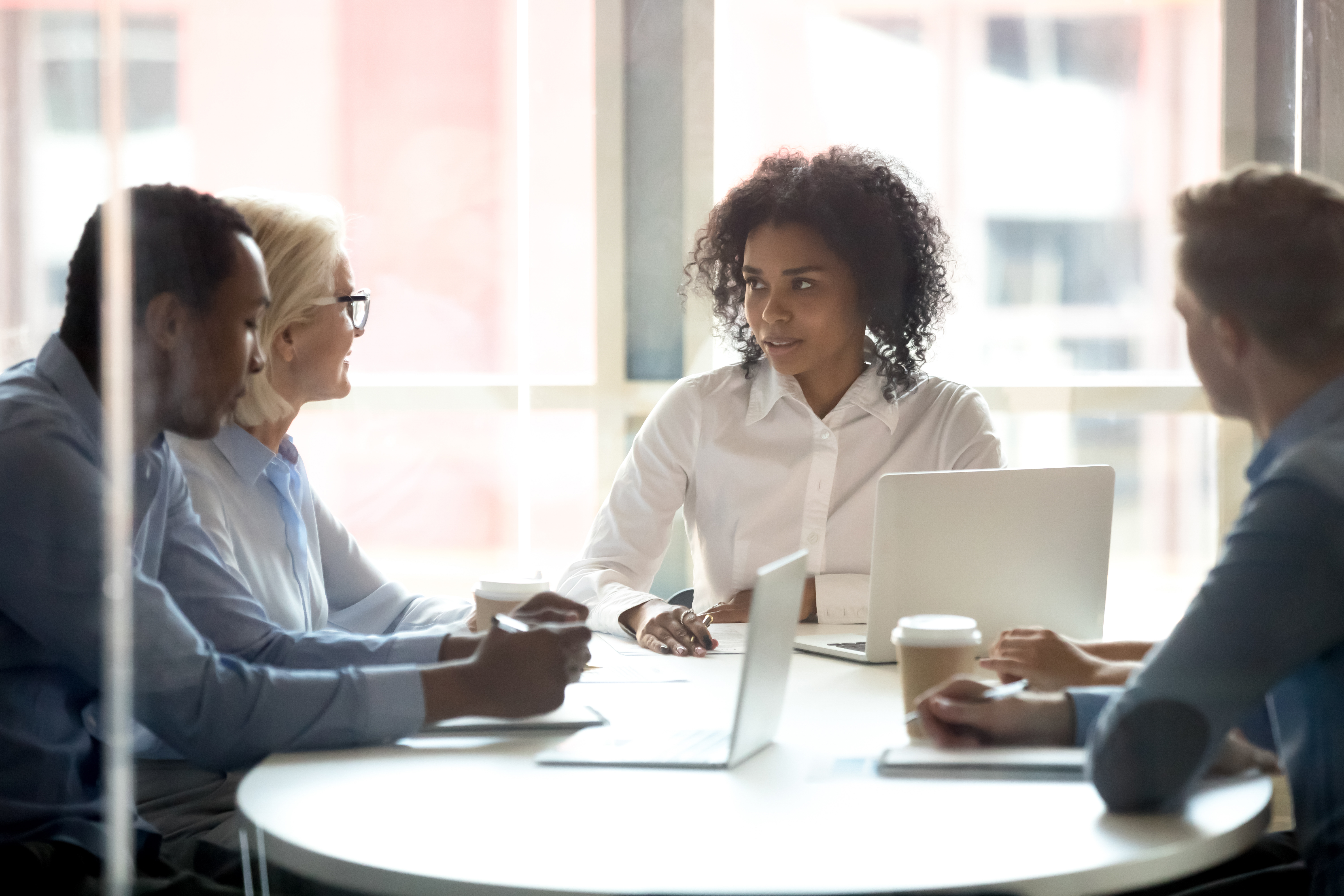 Serious african american female leader talking at diverse group boardroom meeting, multi-ethnic team people employees discussing deal benefits, negotiating on business contract terms with clients