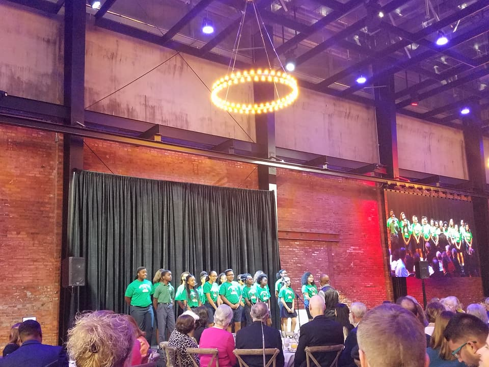 BRP Colleagues in Action pose on stage in matching green t-shirts at charity event