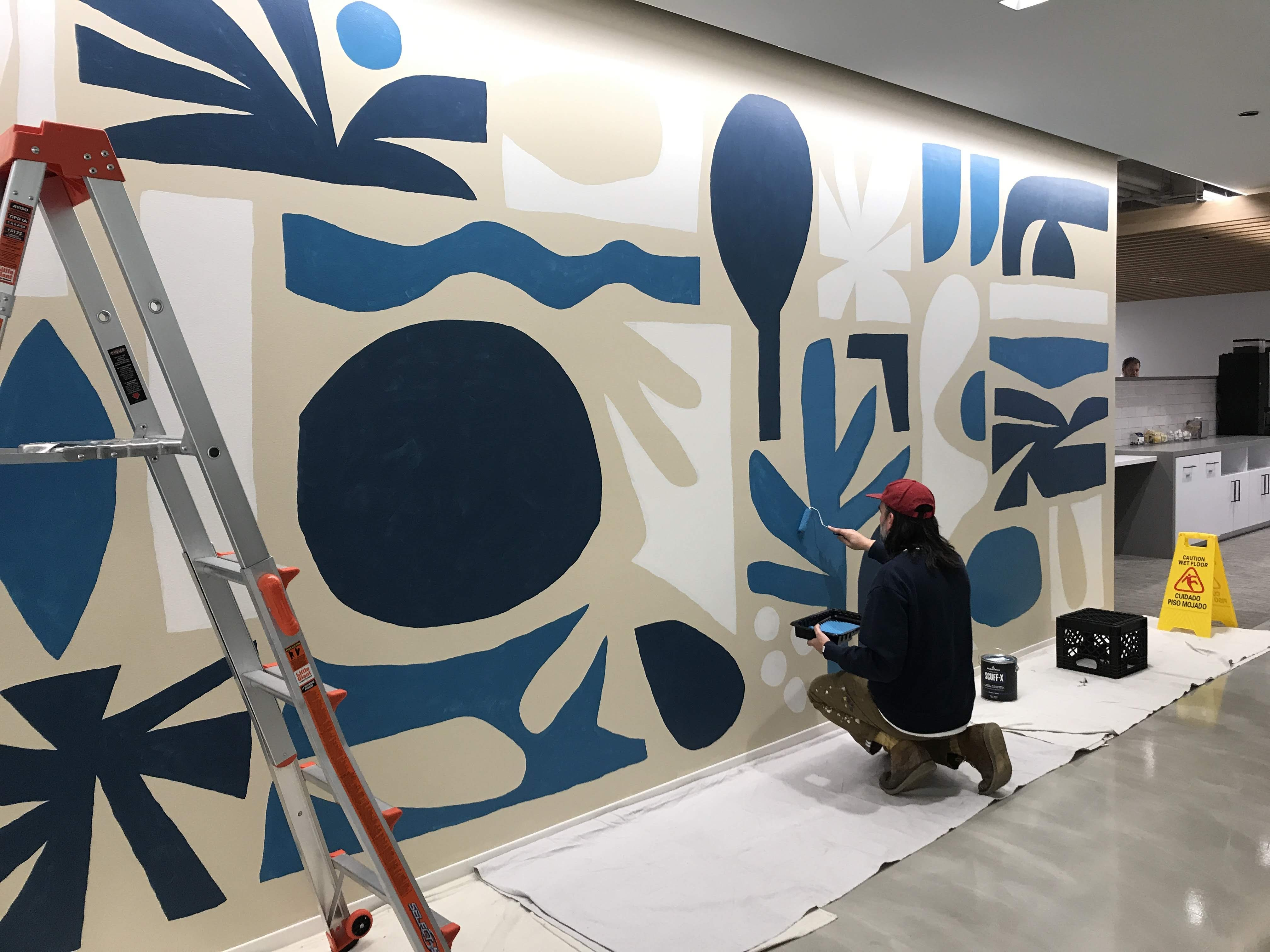 Cody Hudson painting a mural at Brookfield Properties corporate office