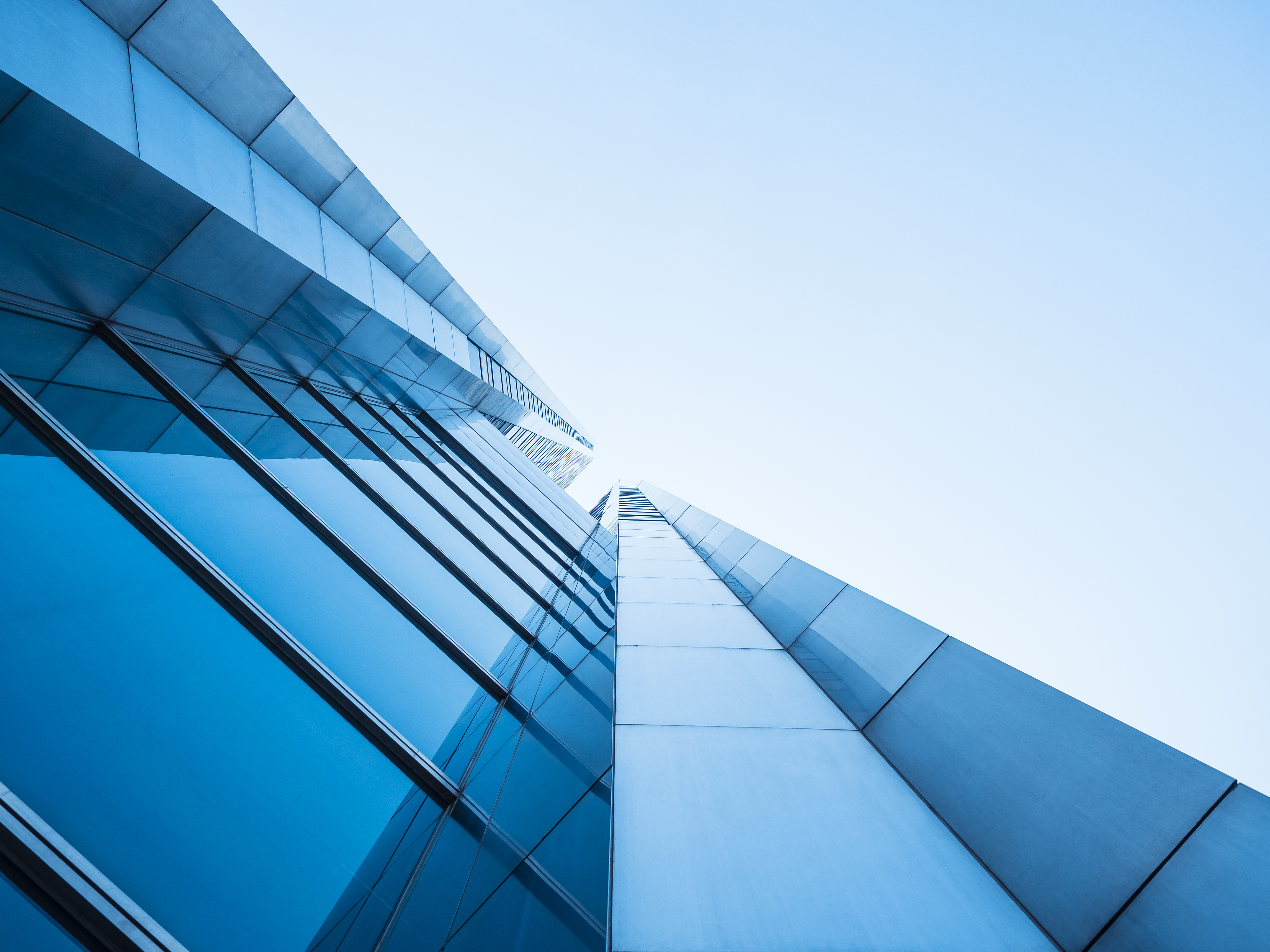 tall commercial building made of gass. photograph taken shot upwards next to blue sky.