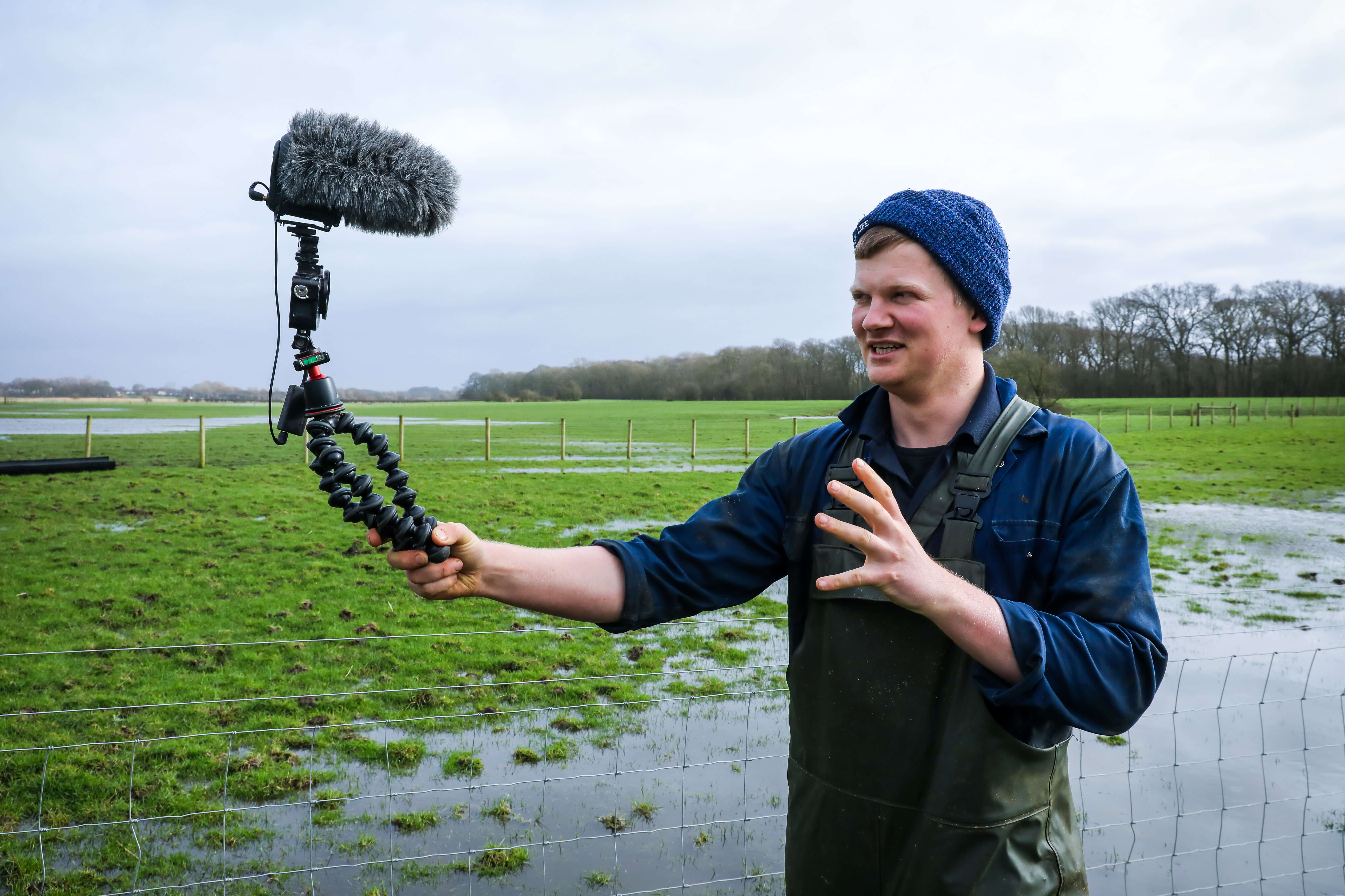 Tom Pemberton on his farm in Lytham St Annes, Lancashire vlogging to camera in a wet field