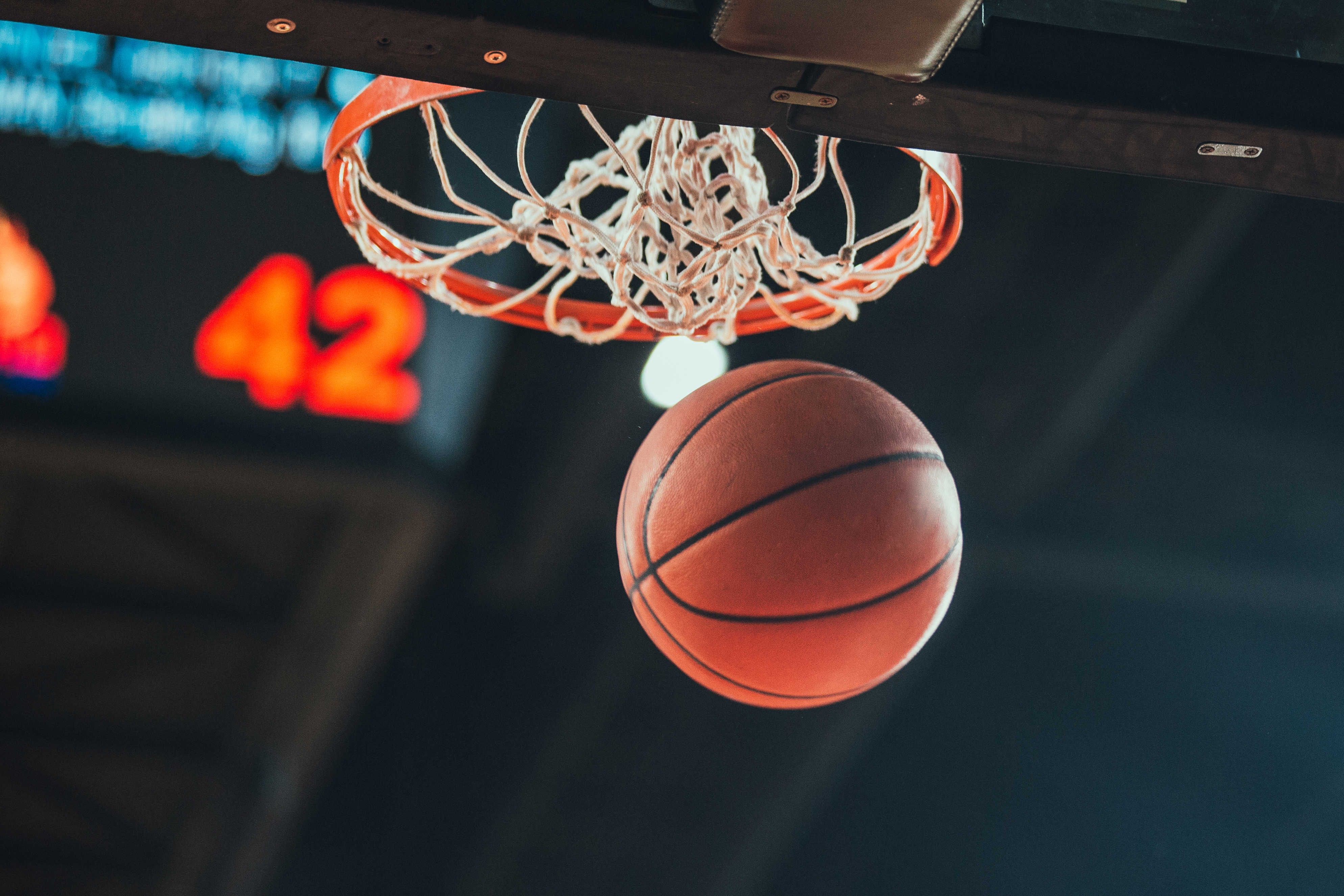 A basketball swooshes through a hoop at a basketball game