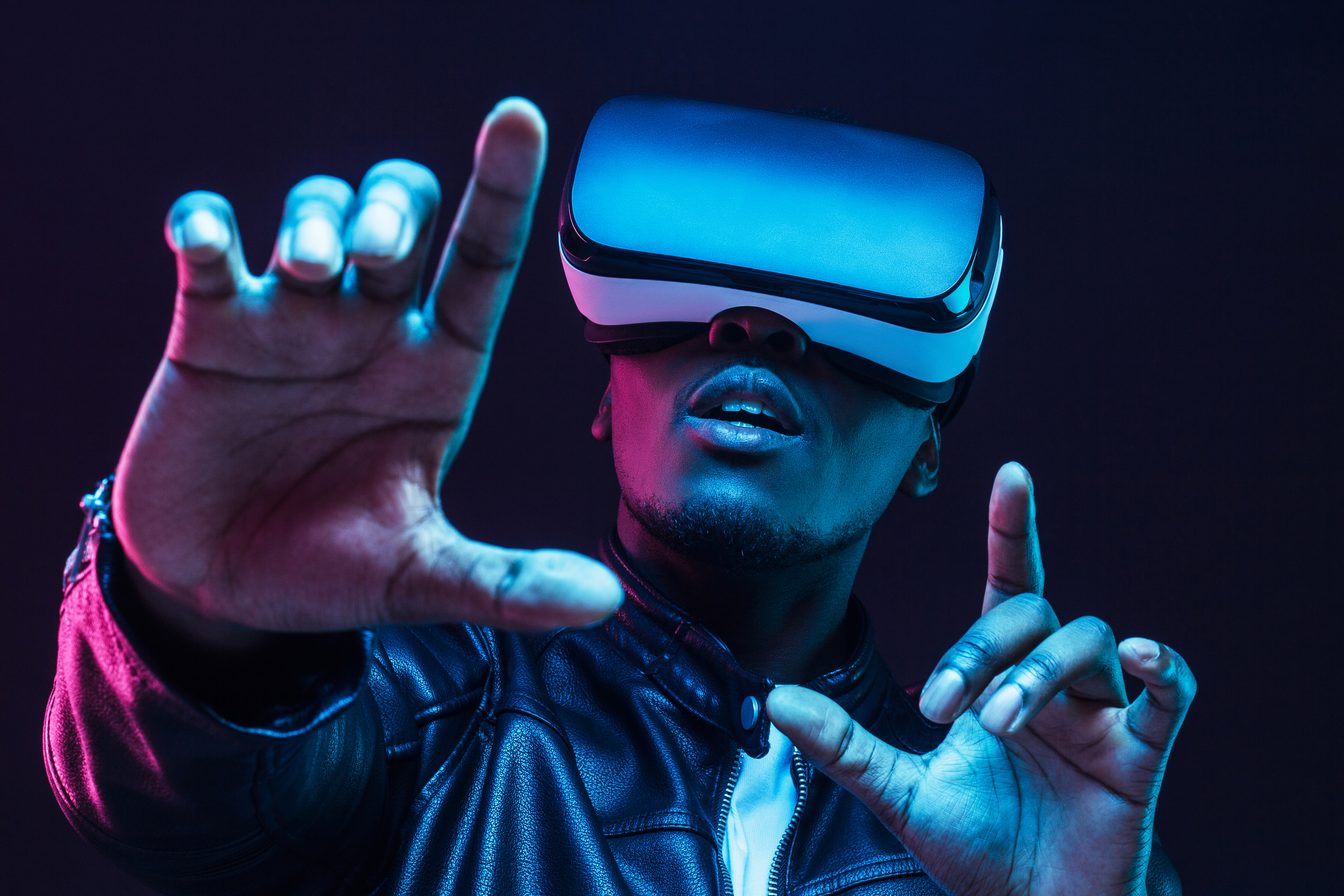 Young african man wearing virtual reality goggles with hands up, isolated on black background