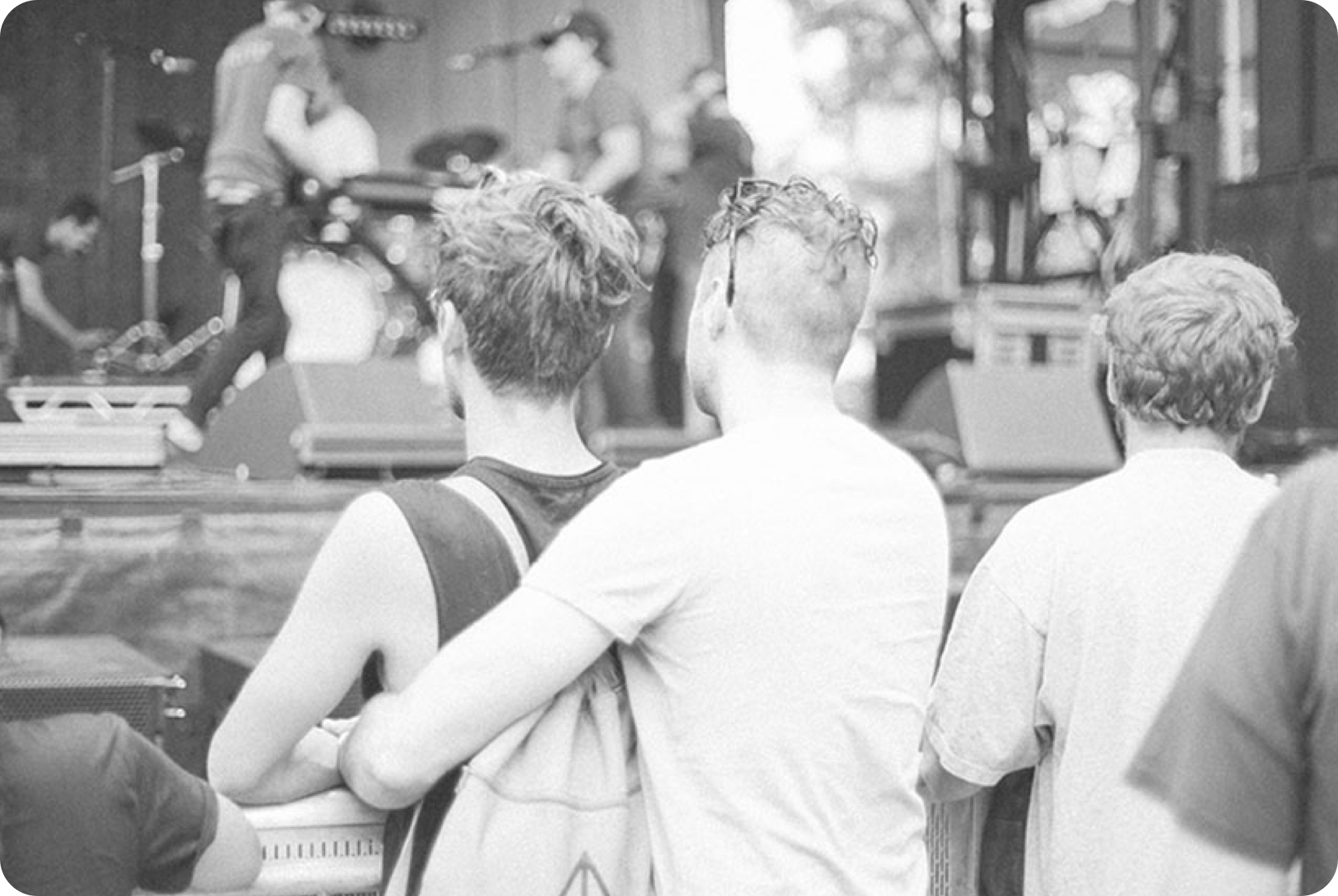 A man embracing another man while viewing  a stage