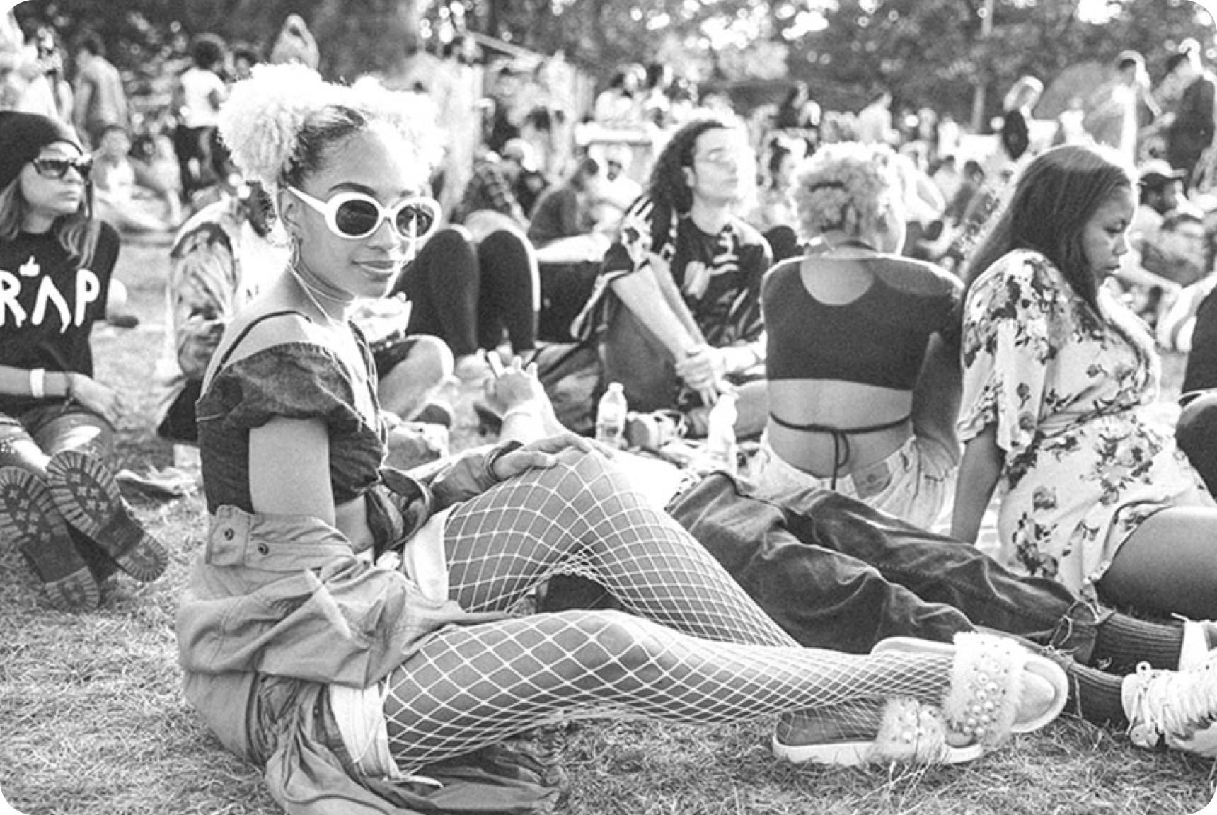 Girl wearing white sunglasses and white fishnets sitting on the grass in a crowd of people