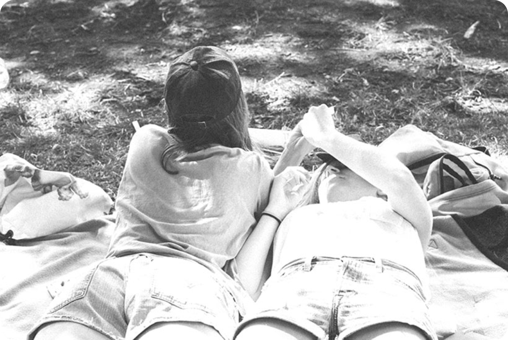 Two girls lying on blankets on the grass