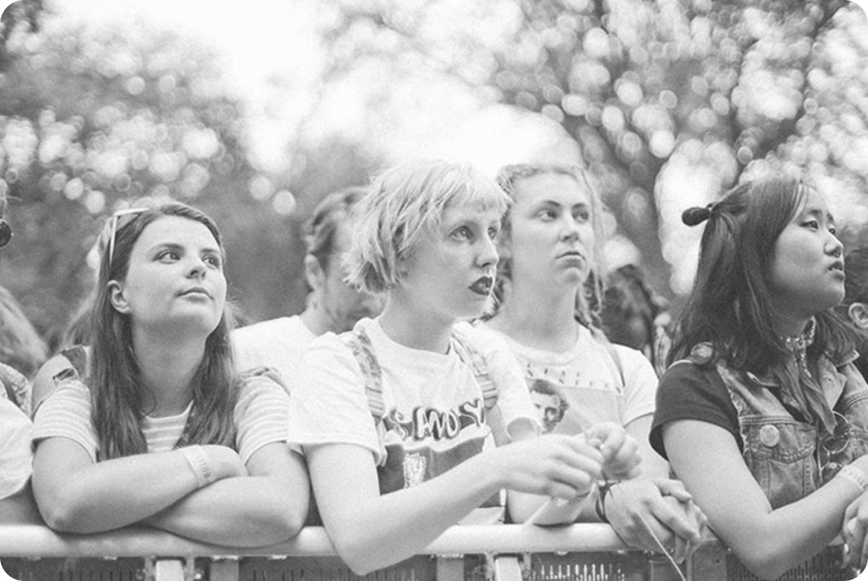 A group of women standing against a barrier watching a music performance