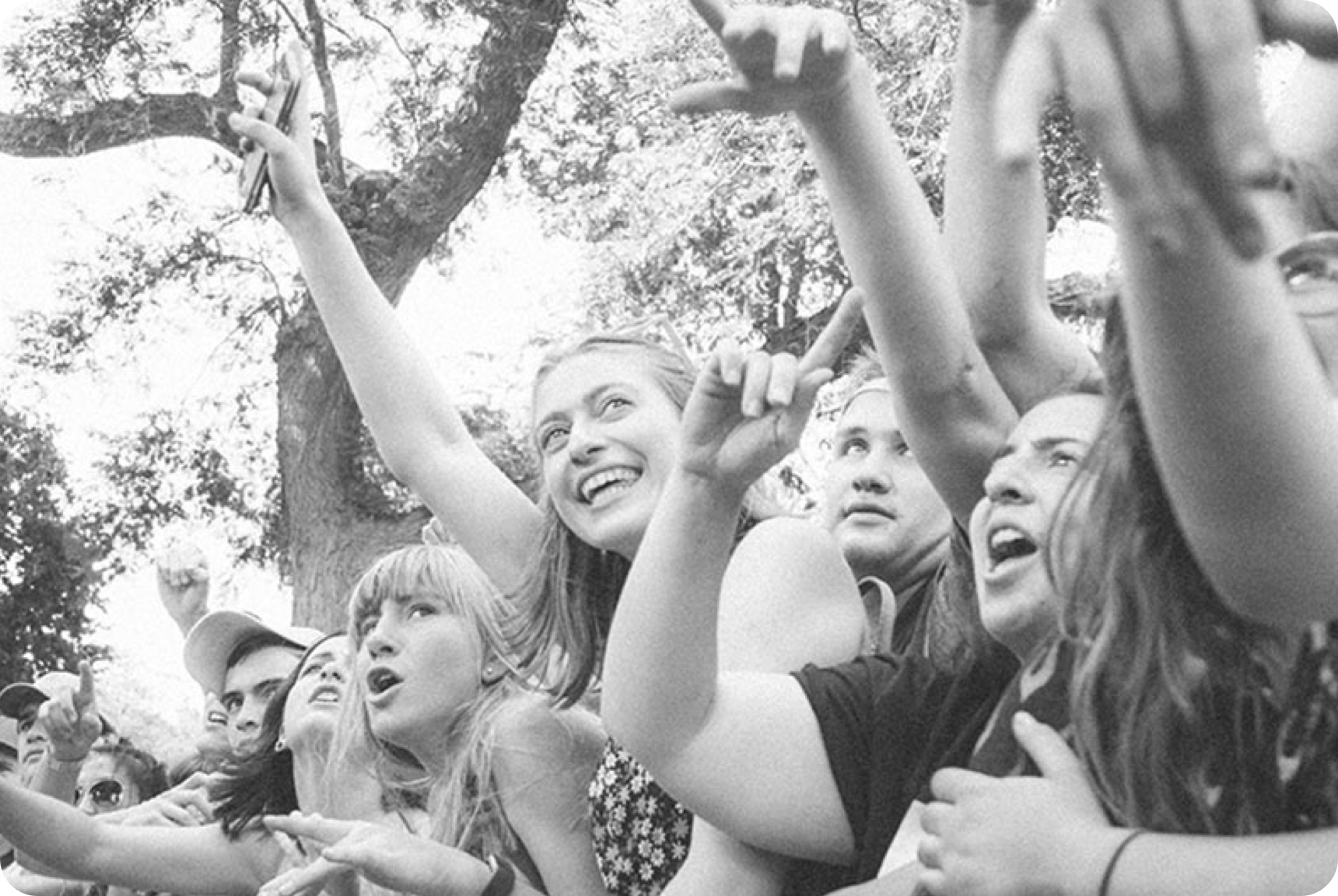 A group of happy young people with their arms extended and smiling