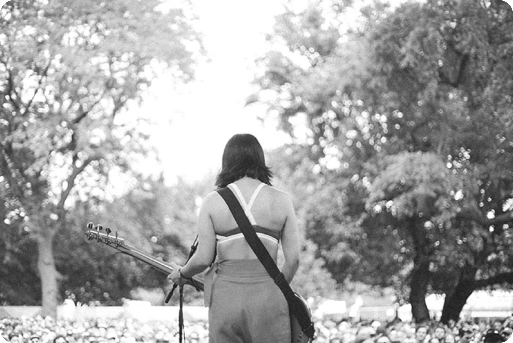 Back view of woman holding guitar overlooking a crowd