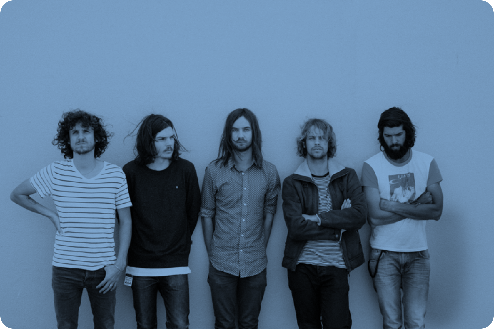 Members of Tame Impala leaning up against a white wall