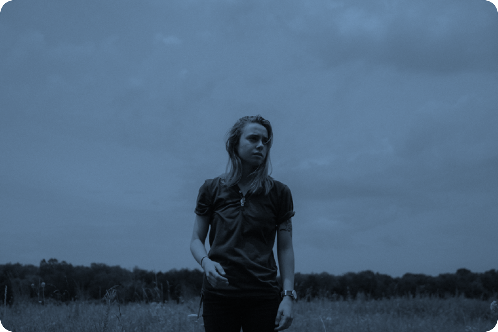 Julien Baker standing in a field of grass