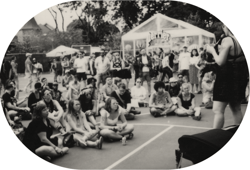 Group of young people sitting on asphalt viewing a performance