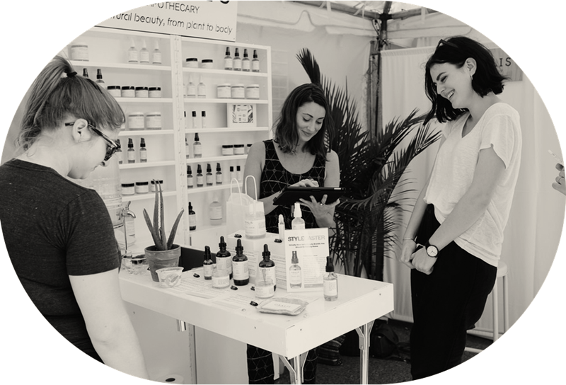 Group of women shopping for skincare products from a vendors tent