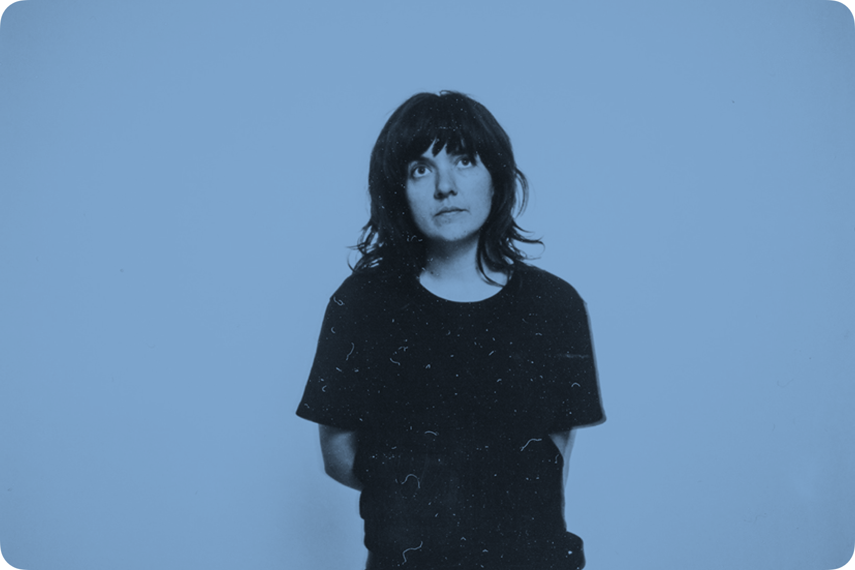 Singer Courtney Barnett looking upwards with her arms behind her back