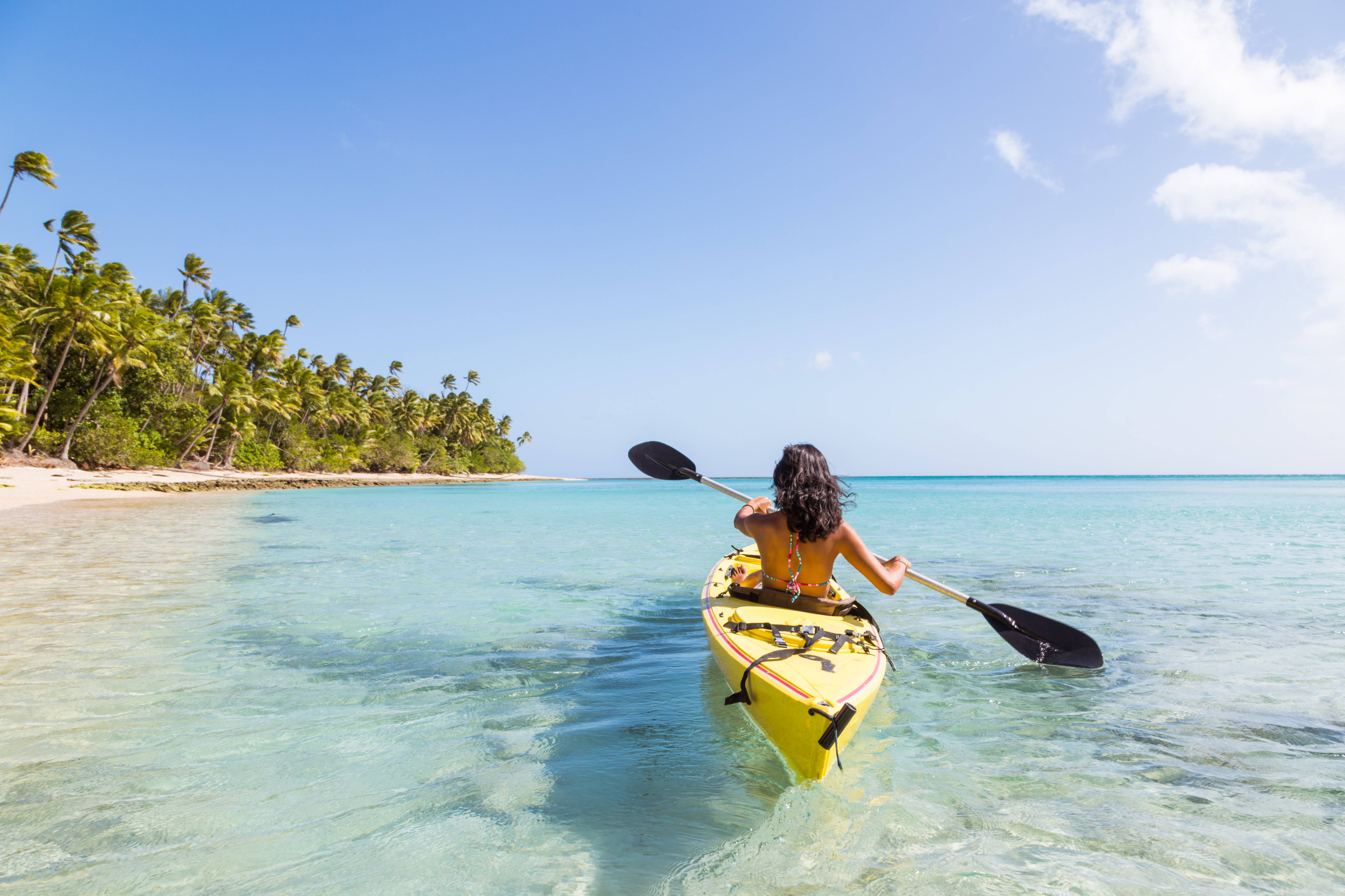 A woman navigates a yellow kayak close to shore at a tropical beach with cystal clear waters.