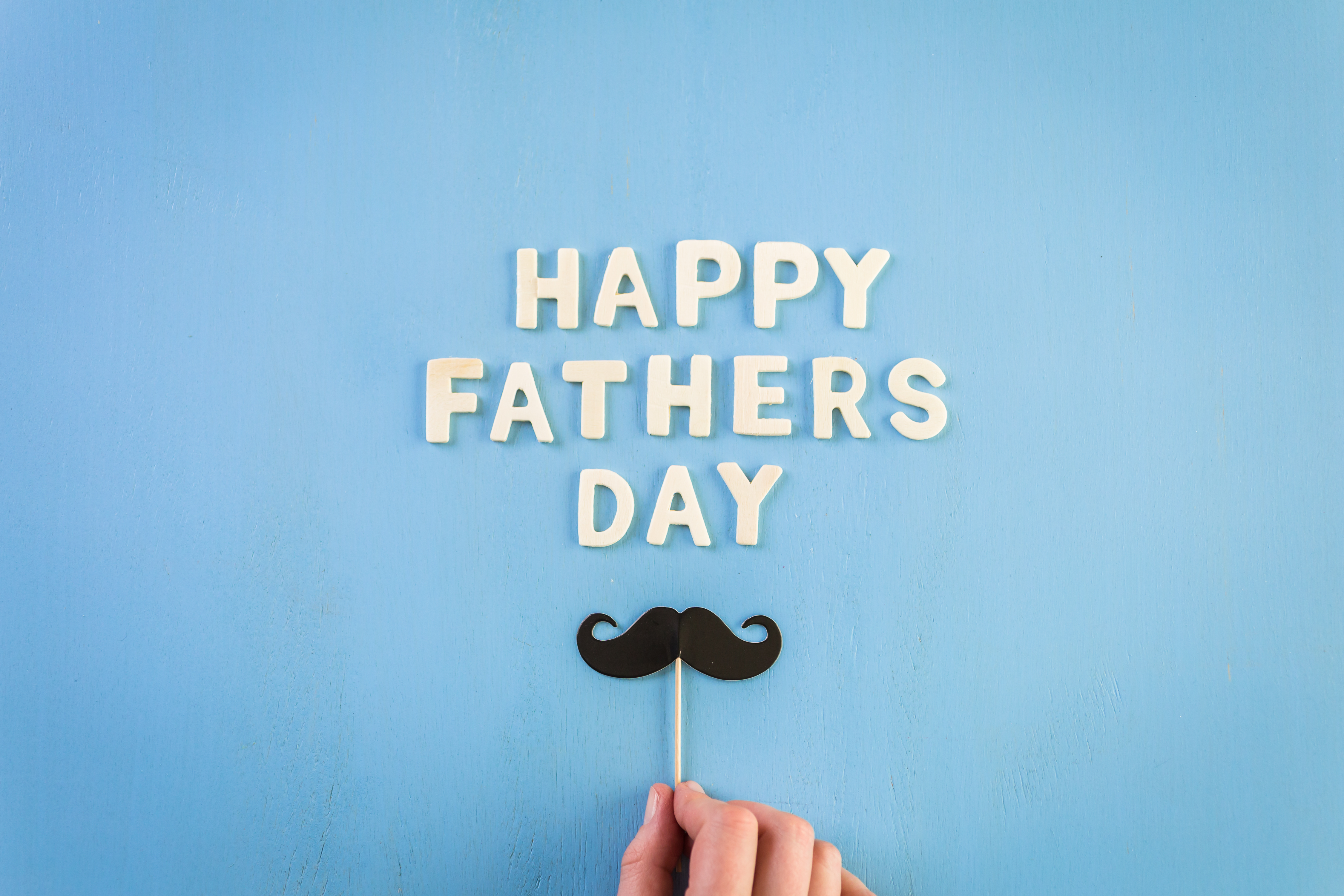 Unfinished wood lettrs sign Happy Father's Day on a painted wood background.