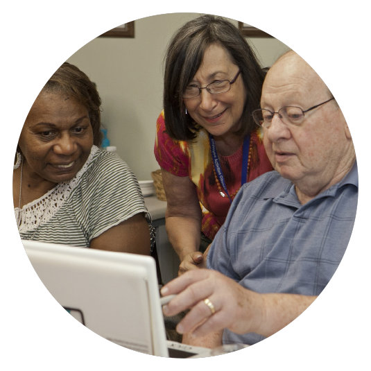 therapist with seniors looking at a computer