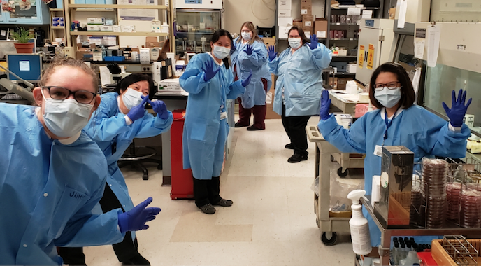 a hospital team in face masks poses