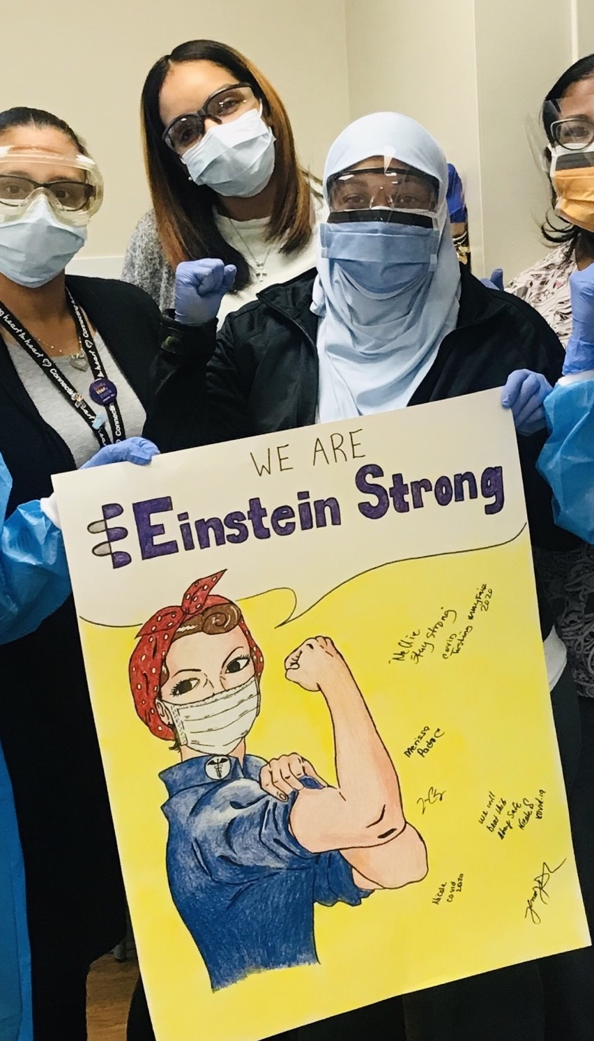 hospital workers in face masks holding a sign that says Einstein Strong