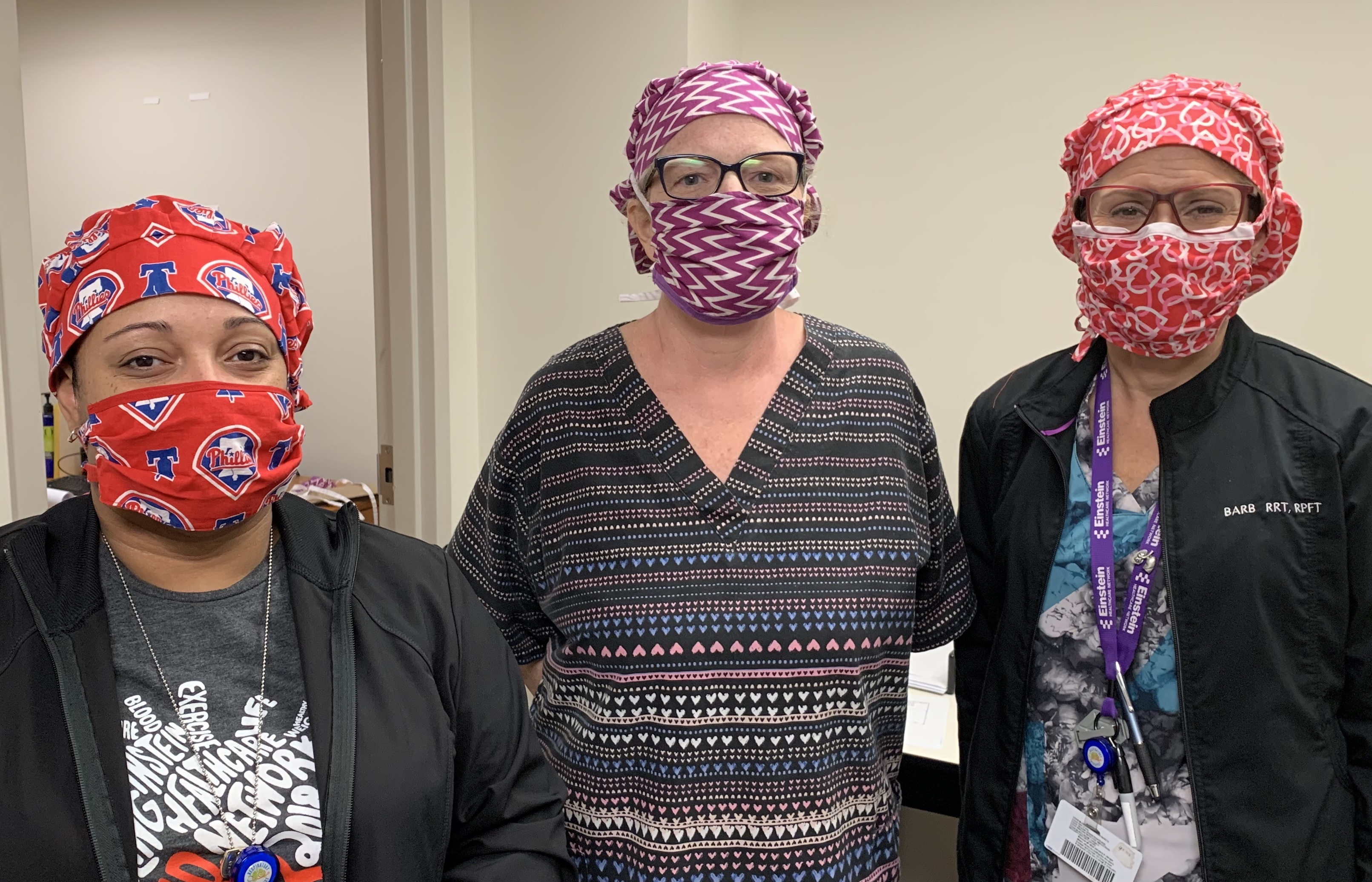three hospital workers pose in masks and head coverings