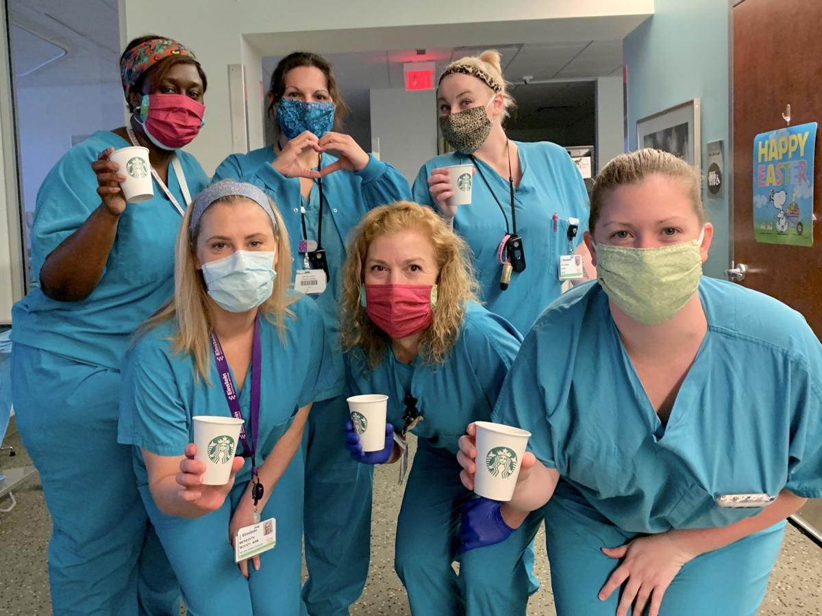 nurses in face masks hold coffee cups and make heart shapes with their hands