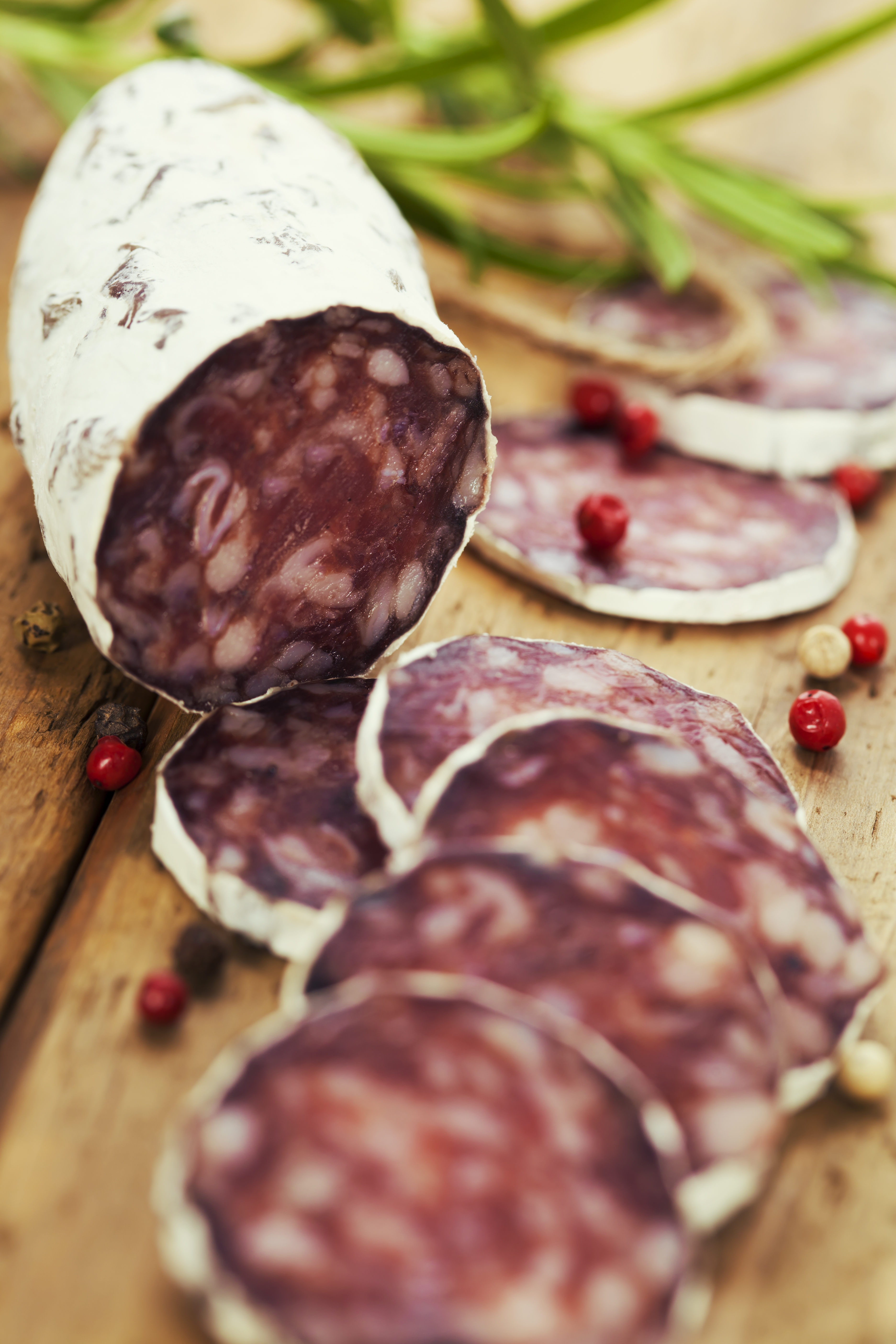 Close-up traditional sliced meat sausage salami on wooden board with rosemary