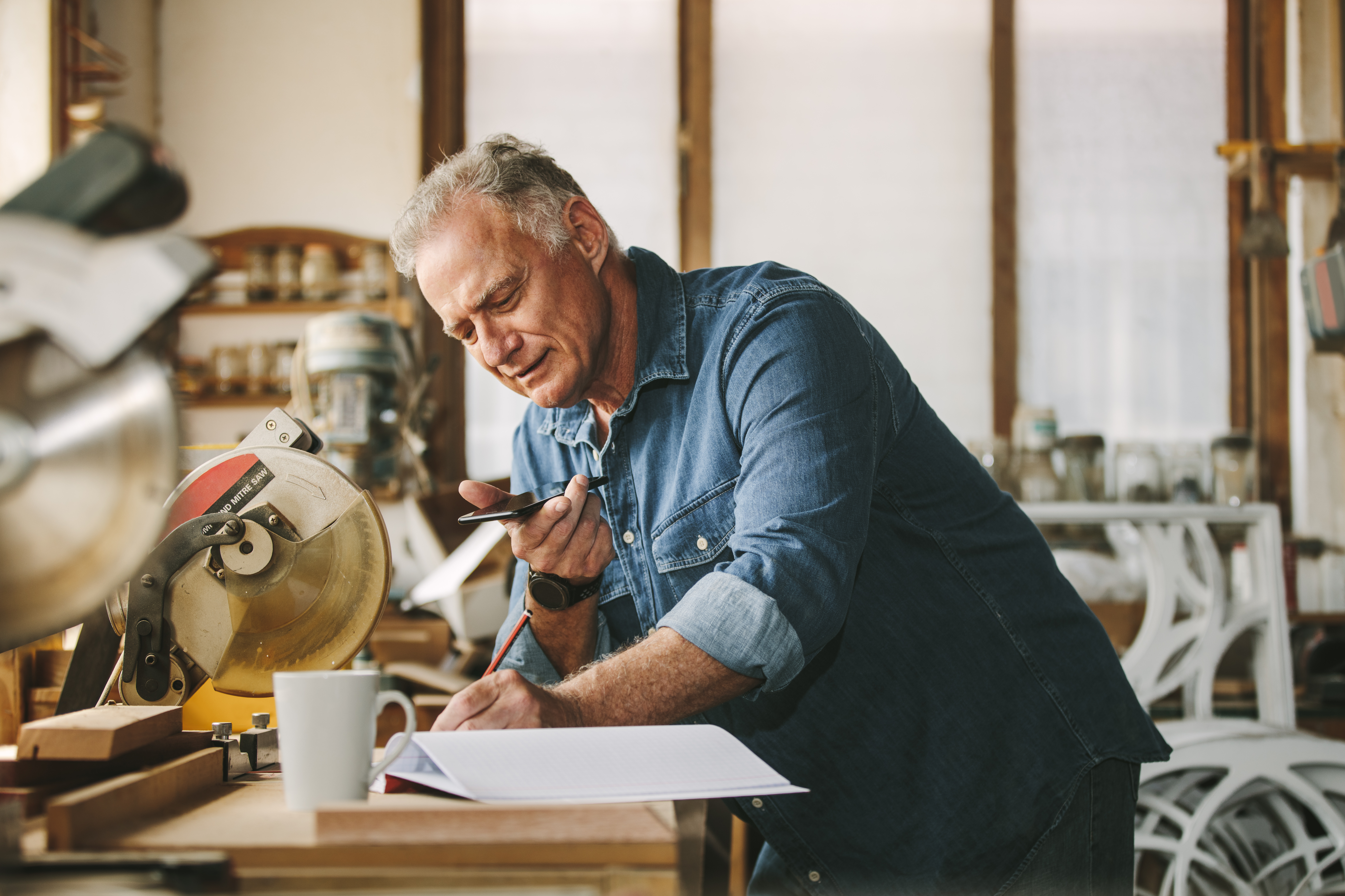 Senior carpenter working at his workshop while standing at desk using mobile phone and writing in a book. Mature man working in carpentry workshop.