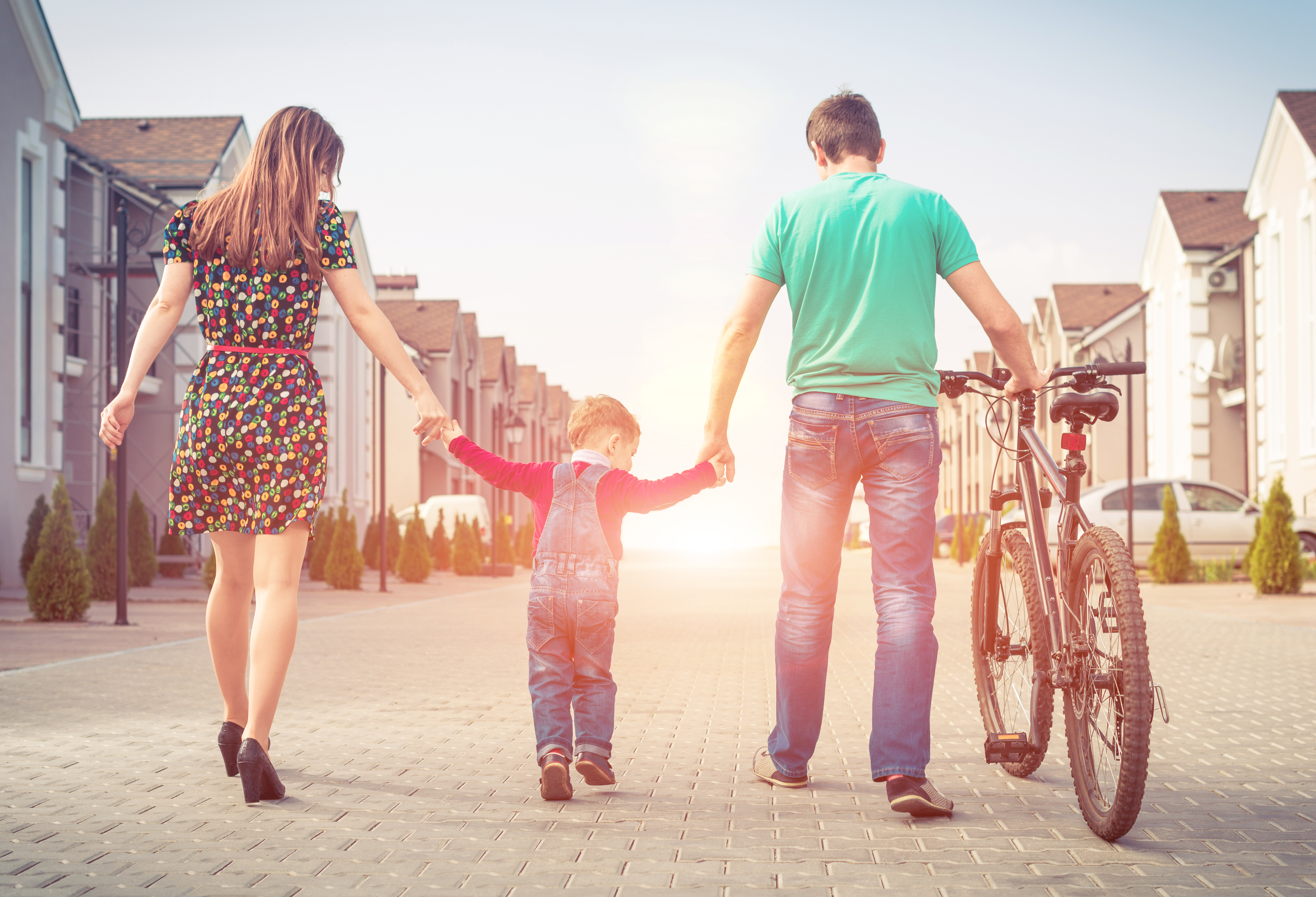 young family with bike walking at uptown street
