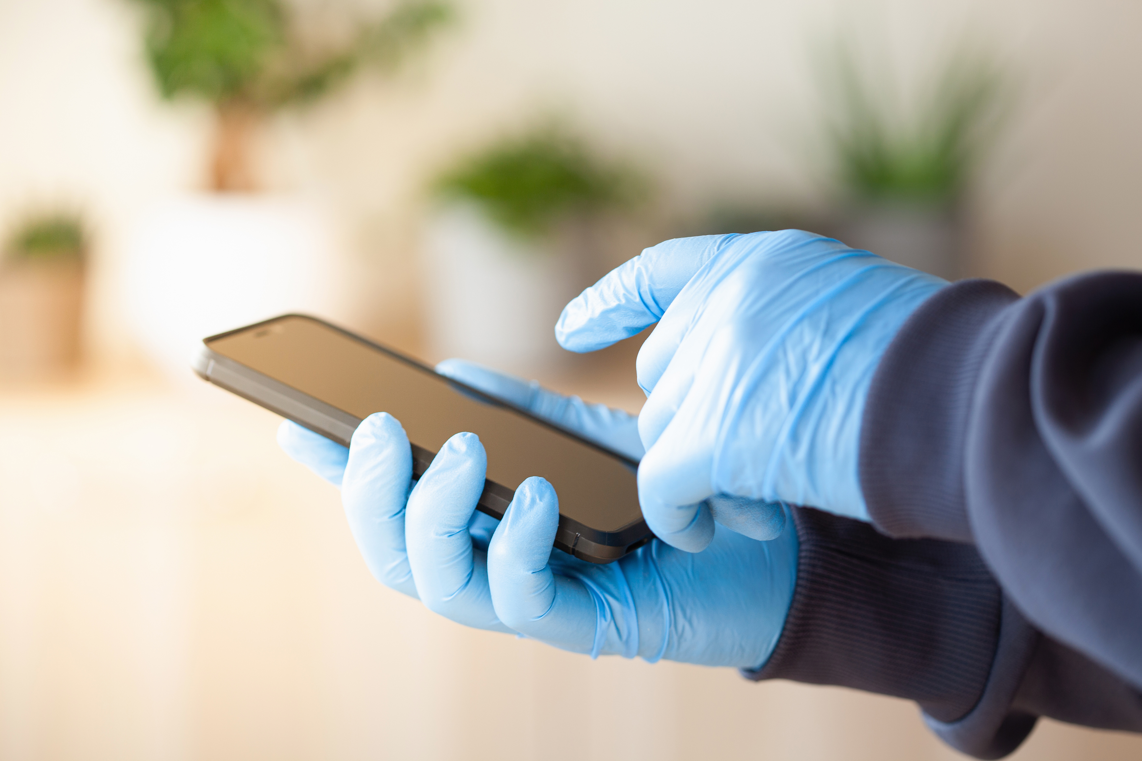 person with rubber gloves using smartphone