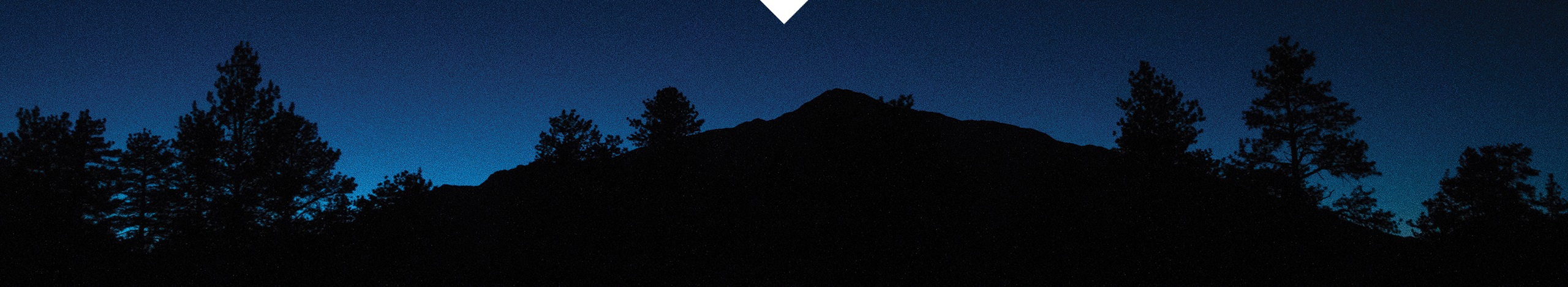 Silhouette of mountains and trees against dark blue night sky