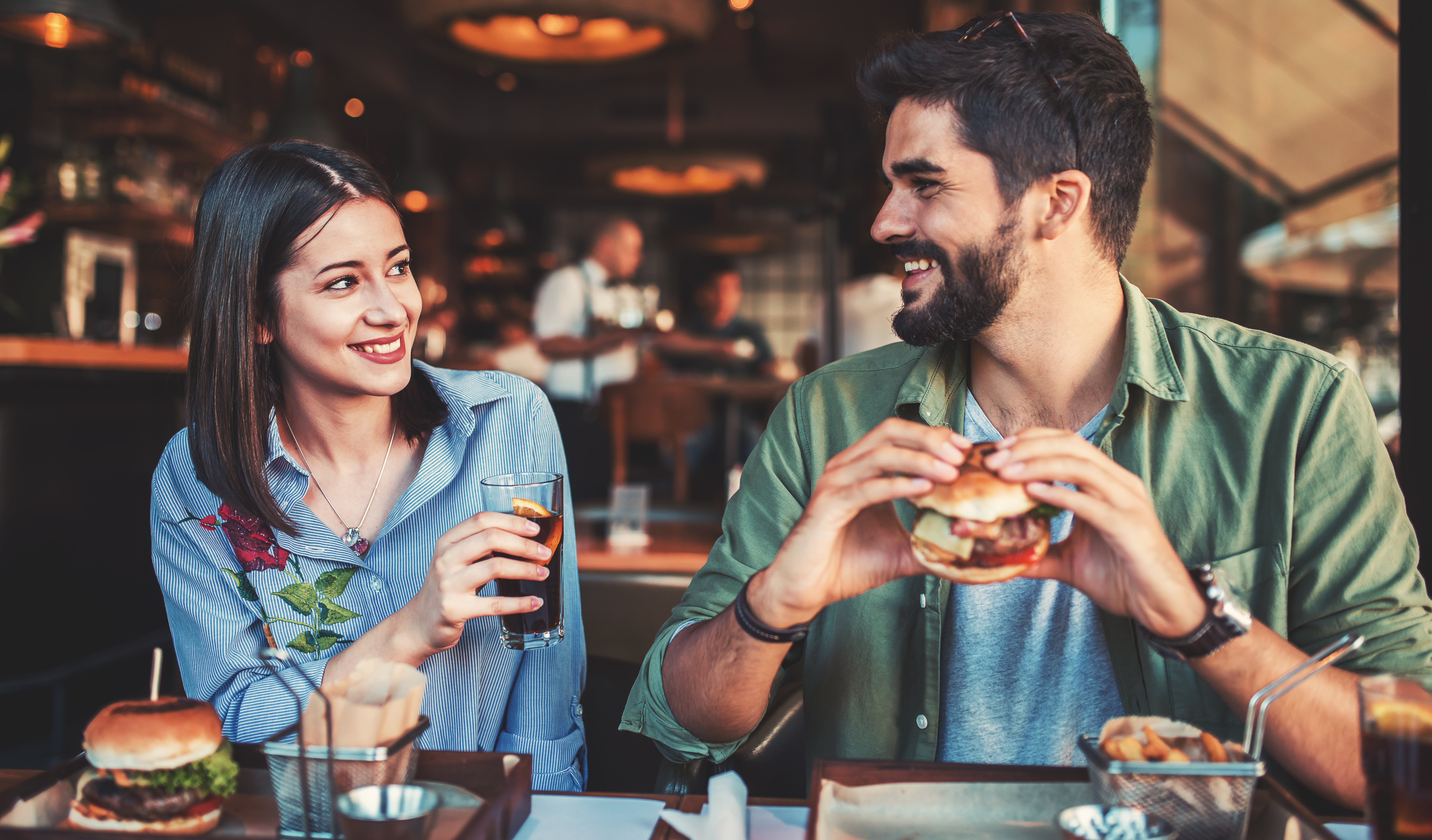 Man and woman enjoying food and drink in a restaurant