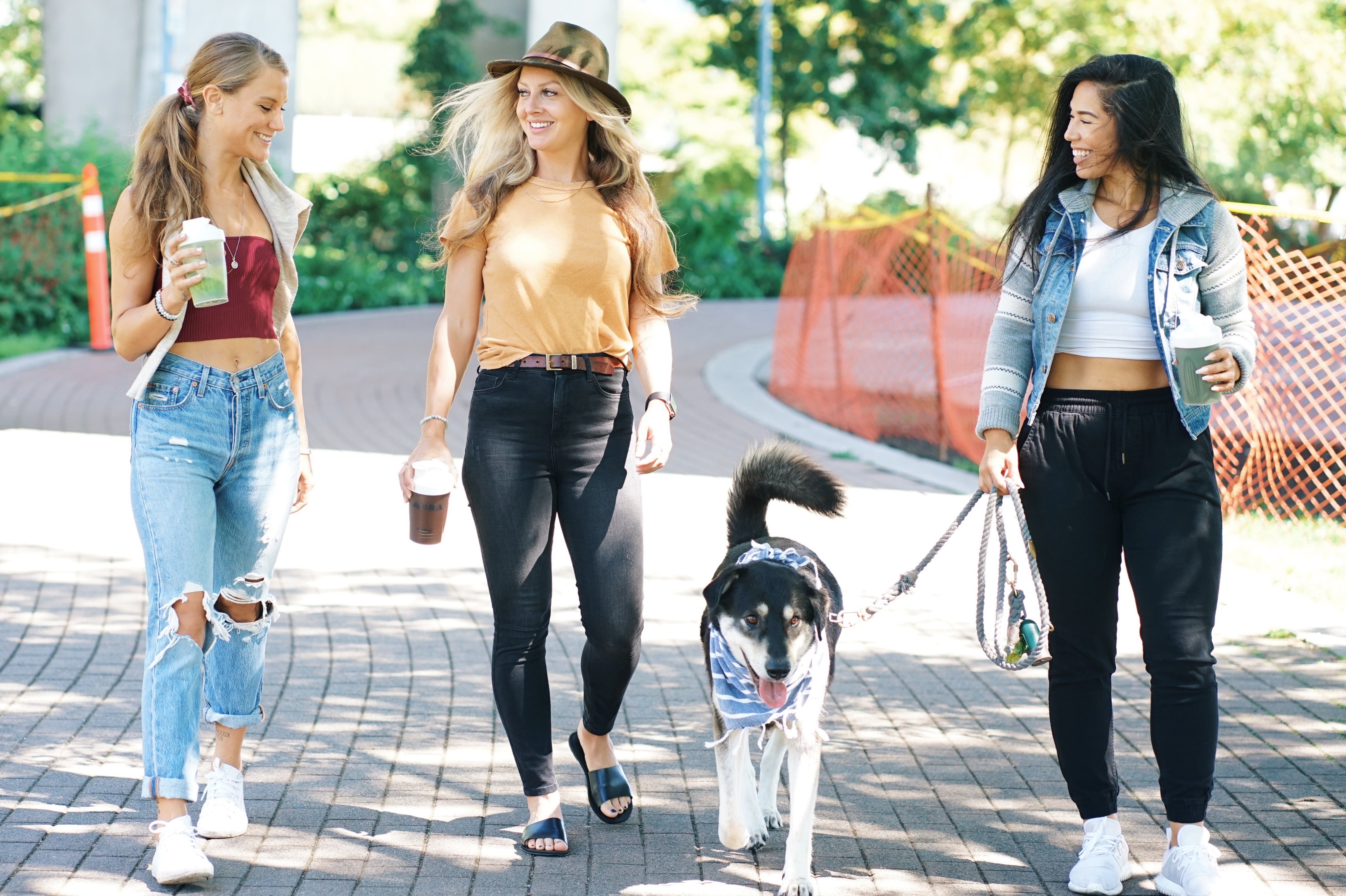 women walking their dog in a park. they are smiling.