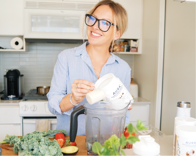 image of Kate Marshall in a kitchen, she is smiling as she prepares a smoothie using Aura product