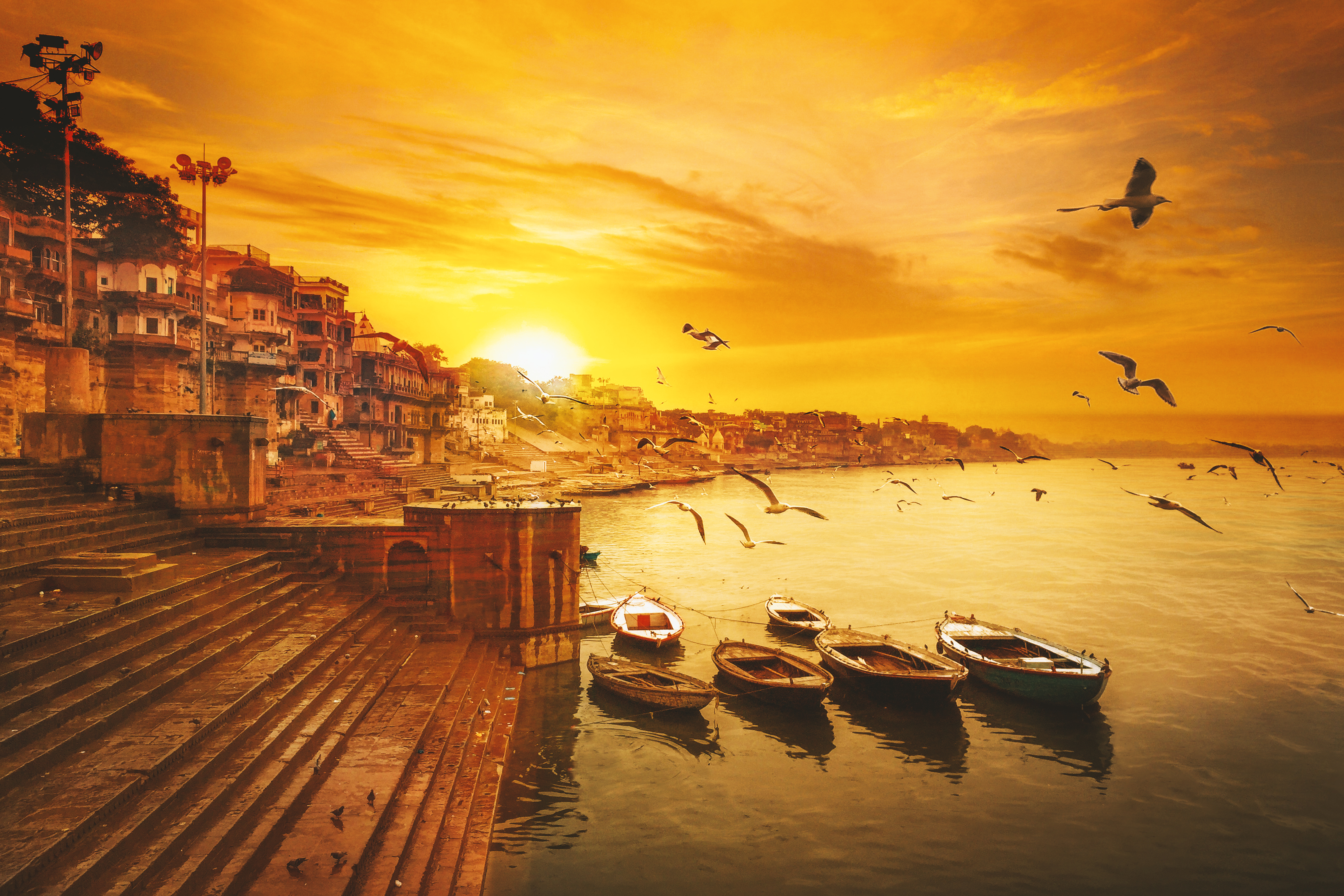 Varanasi Ganges river ghat with ancient city architecture as viewed river at sunset.- Image