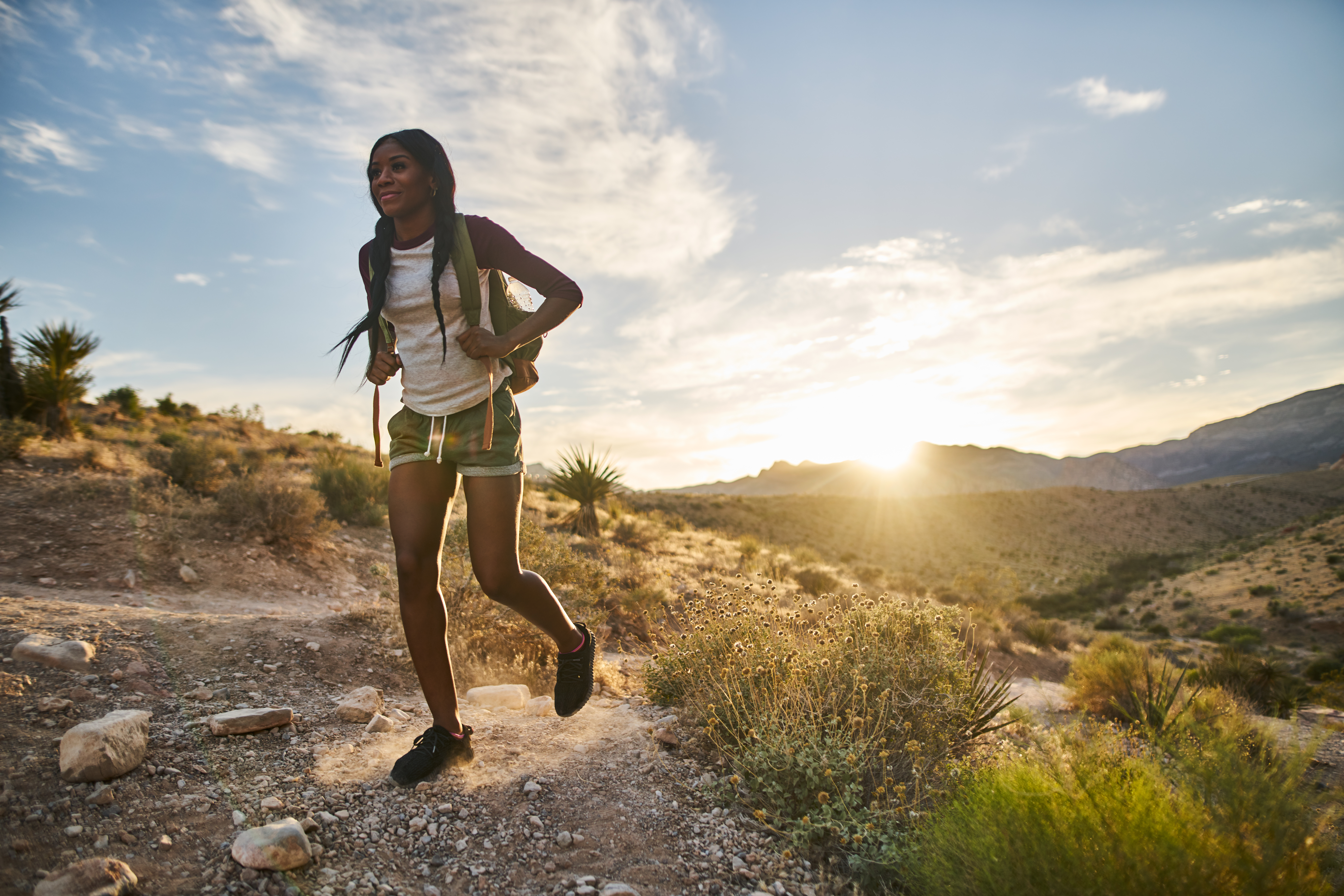 woman hiking at Red Rock Canyon during sunset with backpack shot with lens flare