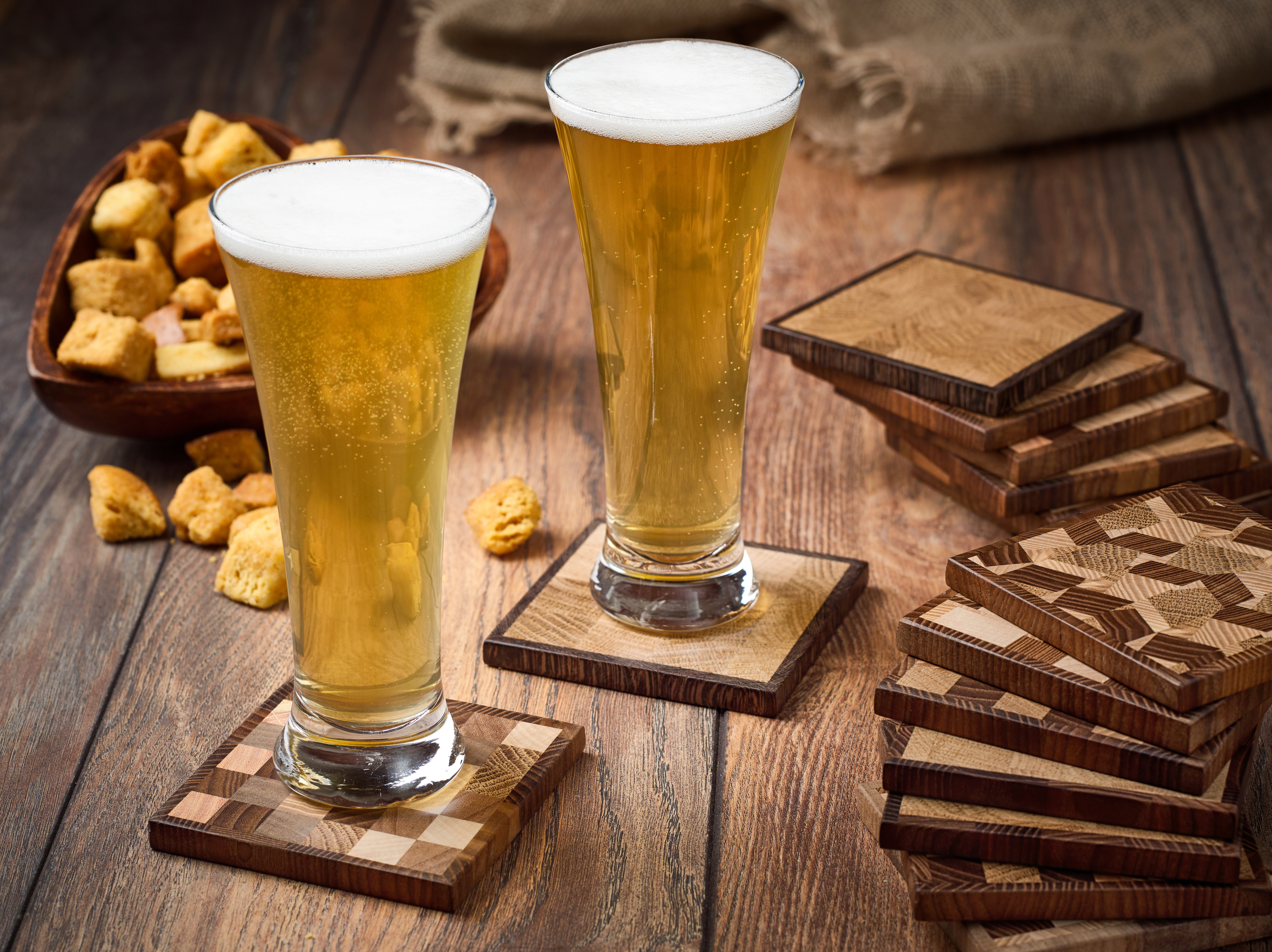 Two glasses of light beer and crackers snacks on a wooden table.