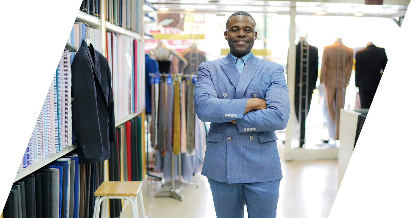 Photo of an African American Male tailor  smiling at the camera as he stand inside his shop