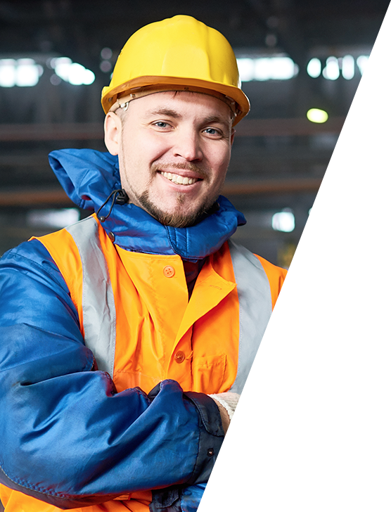 close up photo of a male factory worker wearing a hardhat and smiling directly at the camera