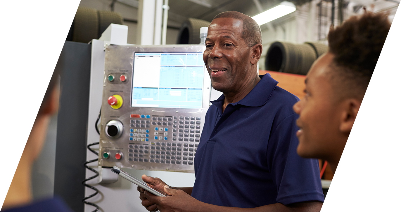 Photo of a male African American manager smiling as he demonstrates how to operate a machine to two younger African American Males