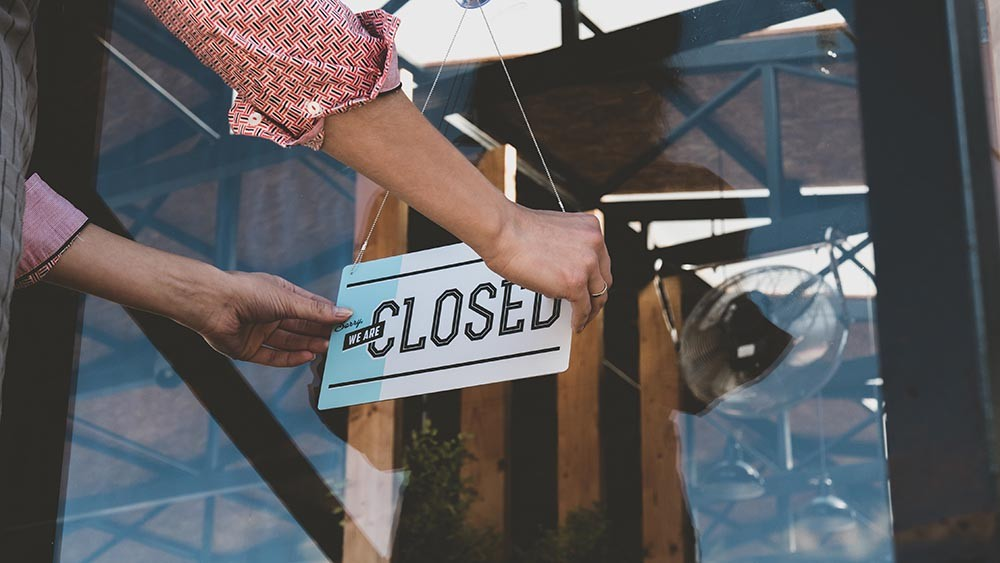 Close up photo of a persons hands as they hang up a closed sign on a retail location door.