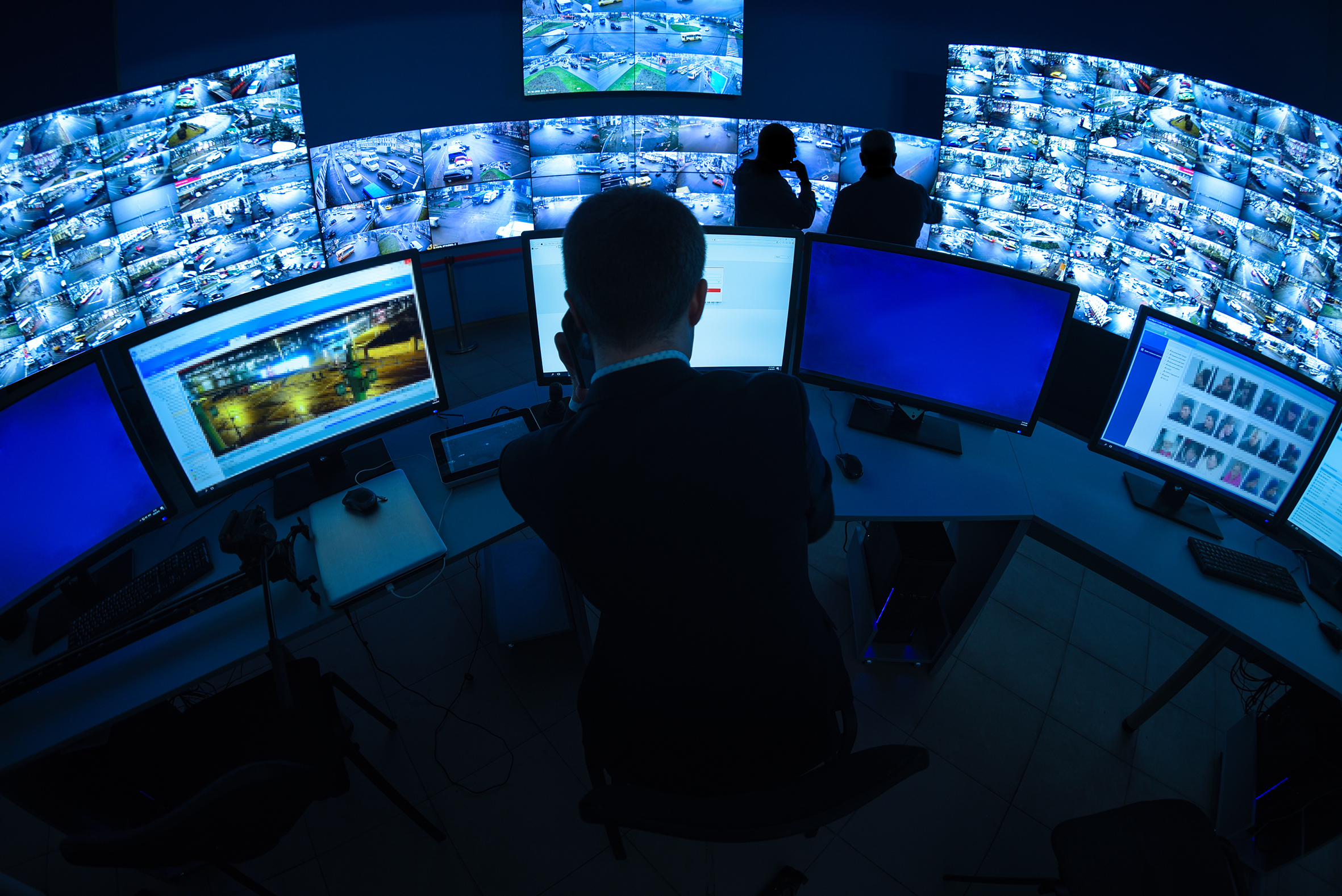 Photo of a security guard in a security monitoring center surrounded by live security camera feeds