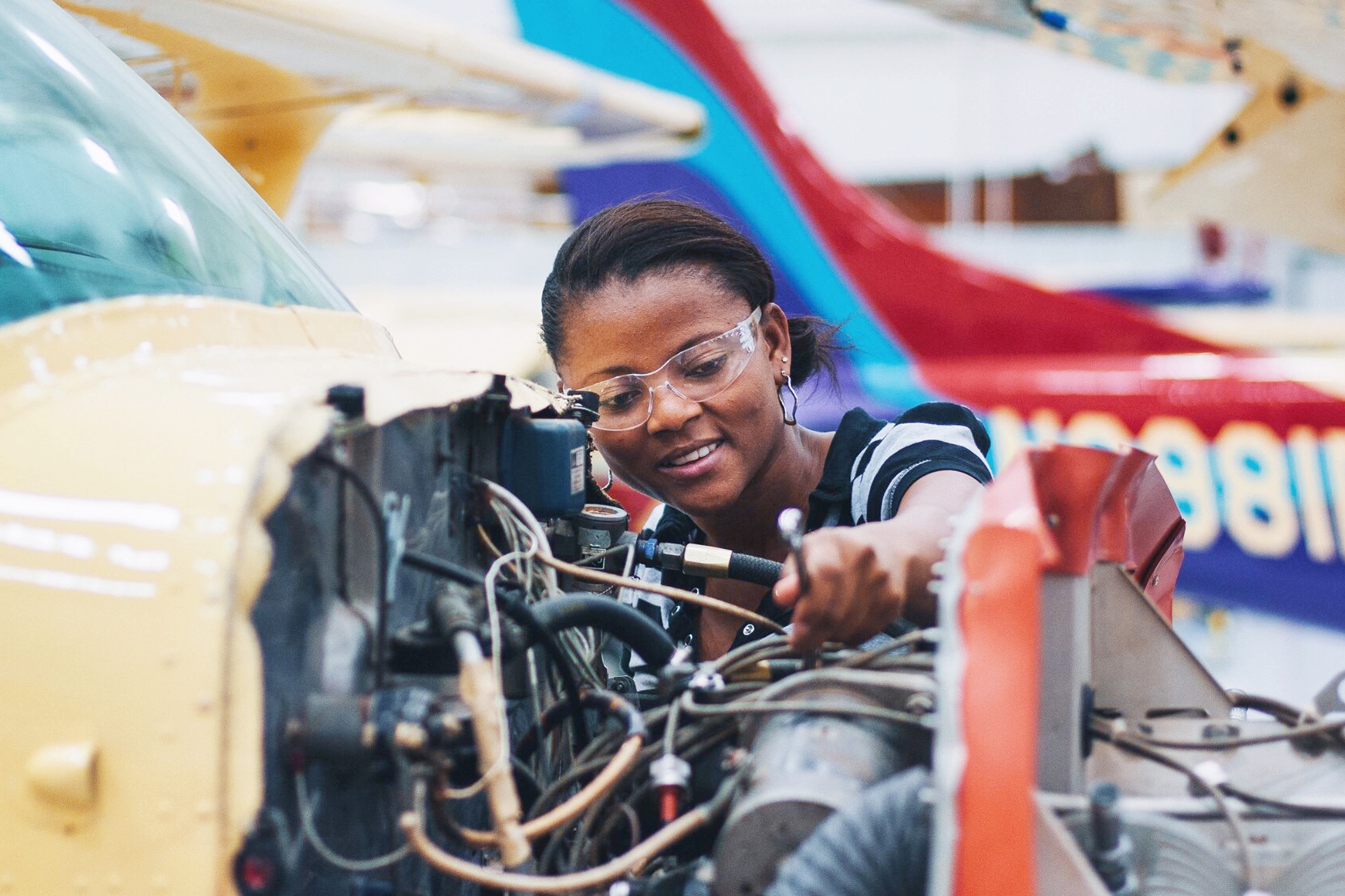 Image of a female mechanic using a wrench working on an aircraft engine