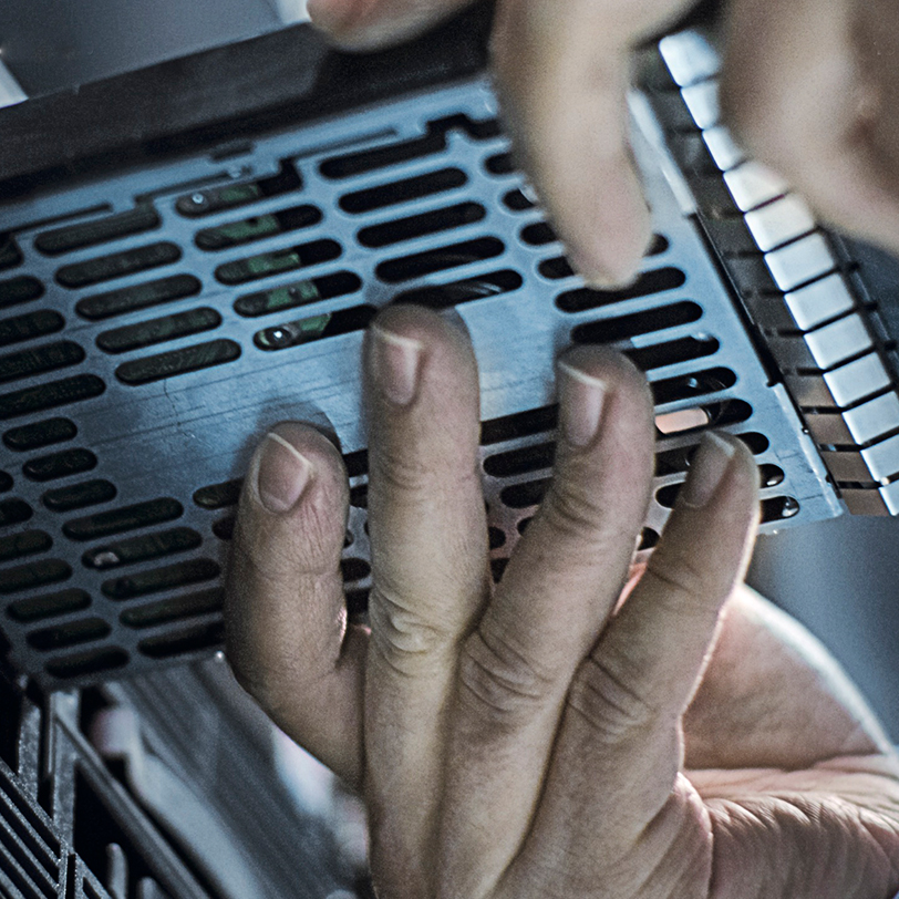 Very close up image of a persons hands swapping out a hard disk drive on a server in a data center rom