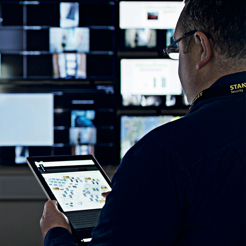Image from over the shoulder of a STANLEY employee looking at an ipad and configuring the security system for a data center customer