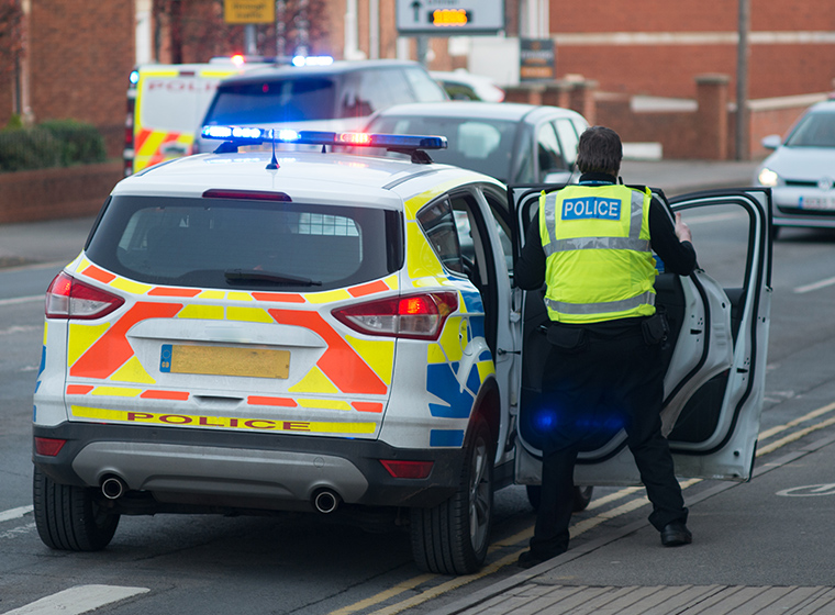 Photo of the back of a UK policeman opening the rear driver side door of his police car