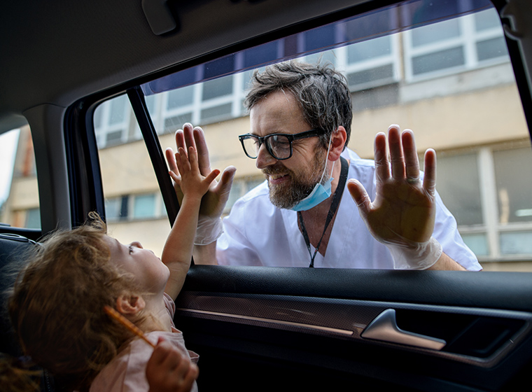 Photo shot inside a car looking out with a child on one side of the glass holding up her hand. the other side is a Caucasian male doctor with PPE mask holding his hand to the glass also