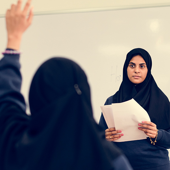 Photo of a Arabic Female School Teacher addressing a class of children as one child raises her hand to ask a question
