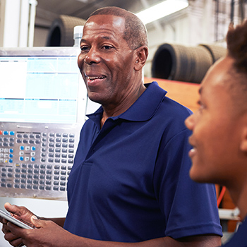 African American male engineer explaining to a a fellow employee how to operate a machine