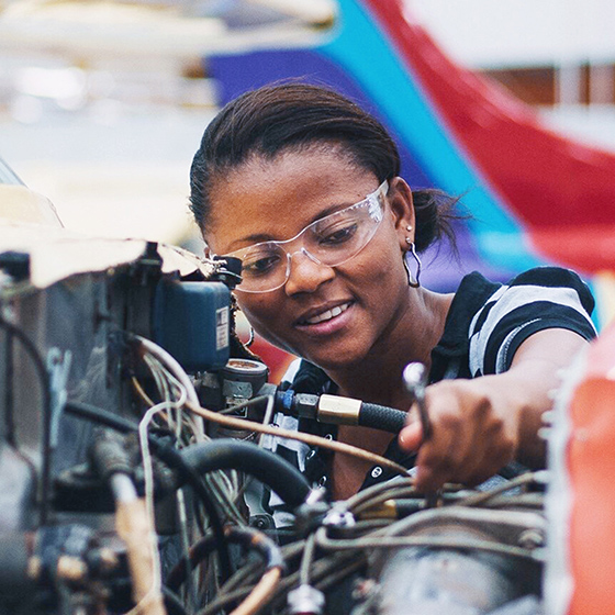 Close up photo of an African American female engineer with safety glasses working on an airplane engine