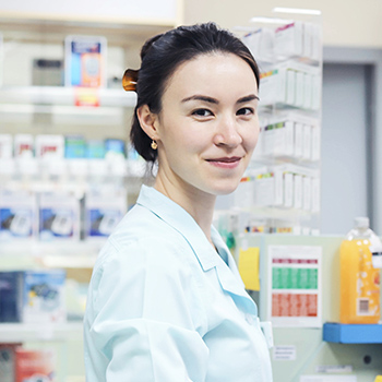 Close up photo of an Asian female Pharmacist behind the counter of a Pharmacy smiling directly at the camera